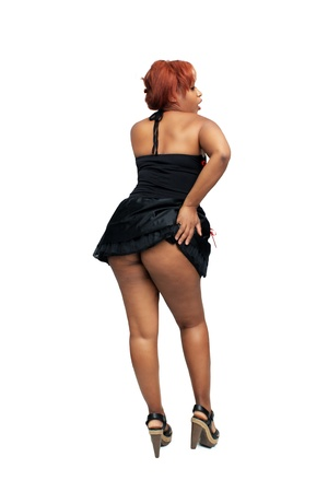 A lovely young black woman with red hair, wearing sexy lingerie that shows her magnificent ass   Isolated on a white background with generous copyspace  photo