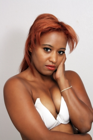 A close-up of a lovely young black woman with red hair, wearing a white bra