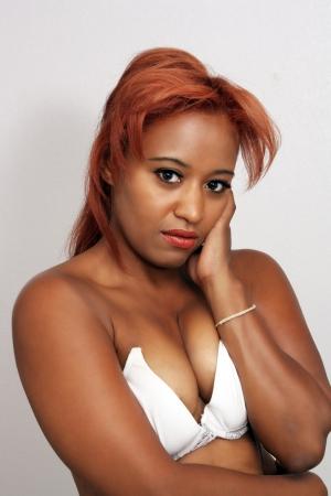 tetas: Un primer plano de una hermosa mujer joven negro con el pelo rojo, que llevaba un sujetador blanco