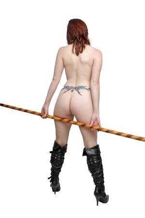 Una hermosa pelirroja desnuda joven vestida s�lo con botas hasta el muslo y sosteniendo un bast�n bo, de espaldas a la c�mara aislada en un fondo blanco con copyspace generoso photo