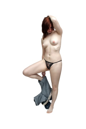 A lovely young topless redhead removes her jeans   Isolated on a white background with generous copyspace  photo
