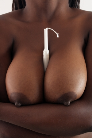 A close-up of a tampon held between two large black female breasts