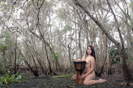 A lovely young, nude brunette kneels nude with a djembe drum, in a wet tropical forest or swamp. Stock Photo - 16882526