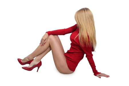 A hot blonde sits, isolated on a white background with generous copyspace