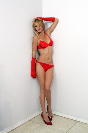 A hot blonde wearing underwear, heels, and long gloves, stands in a corner  photo