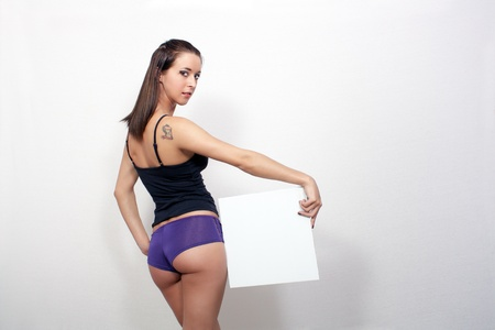 A lovely, sexy, young girl, facing away from the camera and wearing sexy underwear, holds a blank white sign on which you can put your text or graphics. photo