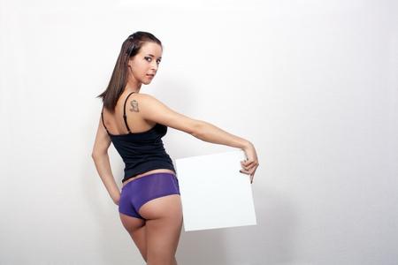 Un precioso, atractivo, joven, de espaldas a la c�mara y con la ropa interior sexy, sostiene un cartel en blanco en la que usted puede poner su texto o gr�ficos. photo