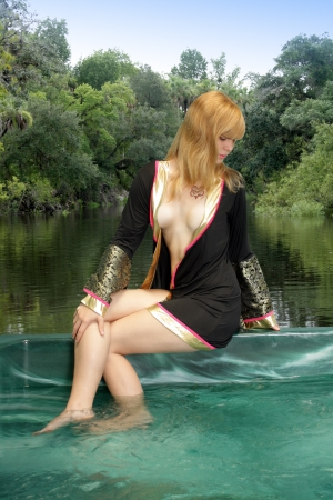 A lovely, young, seminude blonde sits on the edge of her spa, wearing only an oriental bath robe.  A scenic lake with lush tropical vegetation in the background.