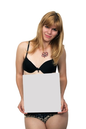 A lovely young blonde wearing her panties and bra, holding a blank grey sign, isolated on a white background  Standard-Bild