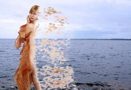 A beautiful young nude blonde with sheer fabric seems to be gathering her particles, or scattering them (depending on your point of view), standing on a tranquil lakeshore.