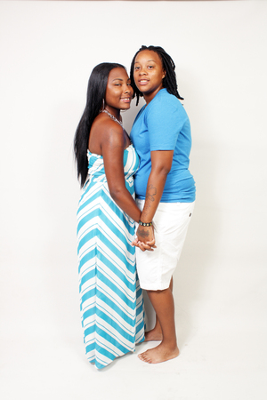 A black lesbian couple, full-length, isolated on an off-white background with generous copyspace.