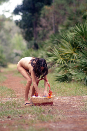 A lovely young, nude brunette bends down to get something from her picnic basket, on a tranquil forest pathway. Standard-Bild