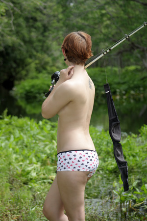 A lovely, sexy, young topless girl with her bra hanging from a fishing rod, stands on a creekbank in a lush, tropical forest  photo