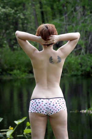 A lovely, sexy, young topless girl stands on a creekbank in a lush, tropical forest  photo