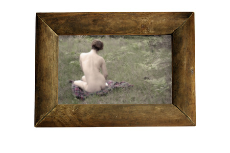 A nude young woman sits on a blanket in a grassy field with her back to the camera, encased in an actual rustic wooden frame.