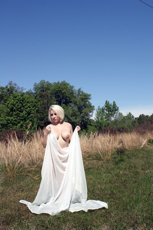 A lovely blonde enjoys nature in her natural state, covered only with sheer, white fabric.