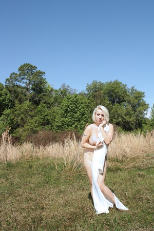A lovely blonde enjoys nature in her natural state, partially covered with sheer, white fabric. Banco de Imagens