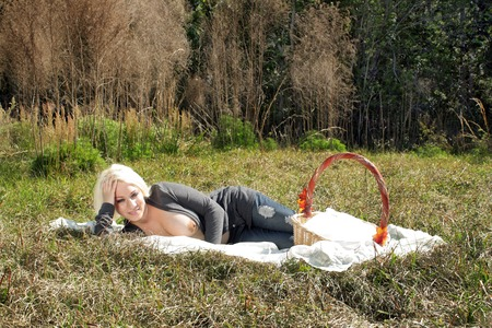 A lovely, busty, topless blonde enjoys a solitary picnic on a bright, sunny day. 免版税图像