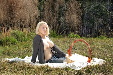 A lovely, busty, topless blonde enjoys a solitary picnic on a bright, sunny day. Standard-Bild