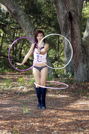 A beautiful young redhead wearing lingerie performs with hoops in a scenic forest. Banco de Imagens