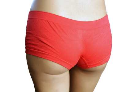 A closeup of a lovely young female ass wearing red underwear, isolated on a white background.