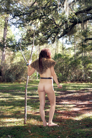 A lovely young naked female hunter wearing a fur shoulder piece with harness, holding a hunting knife and a raw pine forked staff, standing in a scenic forest.