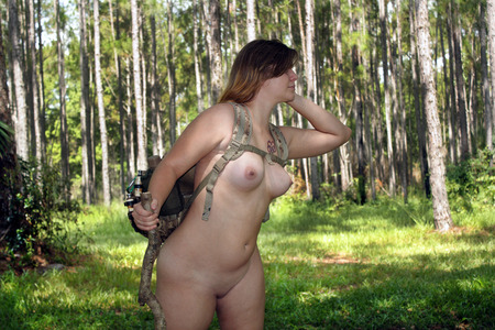 nudity: A beautiful young blonde hiking naked in a scenic forest.