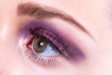 Eye with pink make up and long stitched eyelashes.