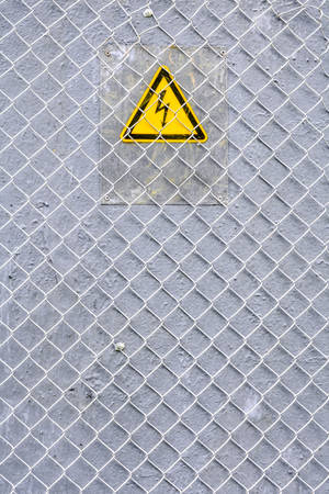 Danger of electrocution yellow sign on gray background with metal wire fence. High voltage warning sign. Electric bolt in yellow triangle safety symbol: caution, risk of electric shock. Stock Photo