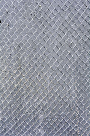 Fence mesh urban background. Wire iron fence on gray painted wall