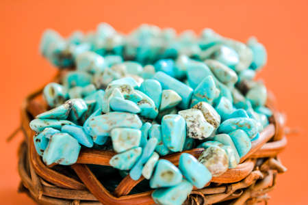 Pile stones of raw Turquoise in small wooden nest on a brown background. Blue and green color stones set. Collection of minerals and natural stones. Heap of stones Stock Photo