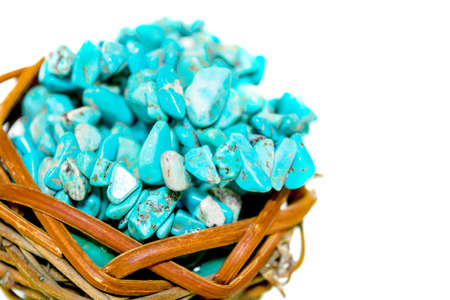Pile stones of raw Turquoise in small wooden nest on a white background. Blue and green color stones set. Collection of minerals and natural stones. Heap of stones Imagens - 105929358