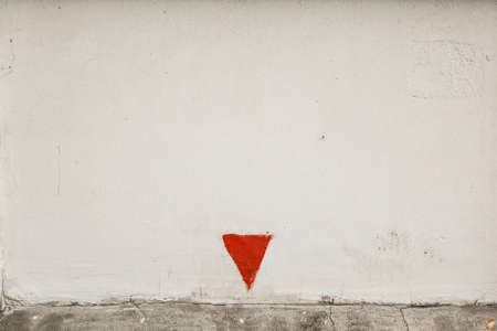 White rough concrete wall with with red arrow turned top down. White wall and painted red triangle 写真素材