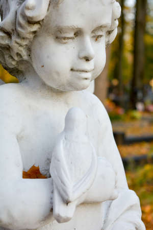 White Stone Sculpture of Guardian Angel in autumn park on cemetry