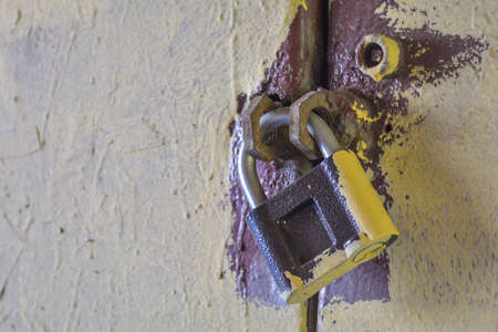 Close up of rusty old key lock on the painted white wall. Dirty padlock on the painted metal door Archivio Fotografico
