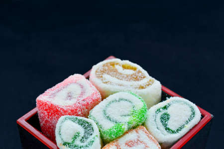 Delicious colorful rolls of Lokum with fruit marmalade jam in japanese style in japanese lacquer black and red wooden box. Tasty dessert of national turkish sweet