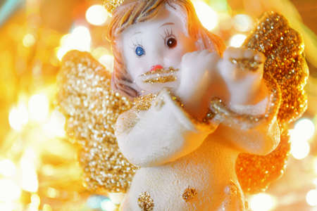 Figurine of little angel with golden shiny wings and halo that plays flute on shining background of blurry flashes. Christmas or New Year picture of cute angel sculpture on bokeh lights background