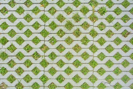 Geometric background of eco floor bricks and green grass. Eco parking texture. Floor stone tile with a rhomb hole for grass. Eco-friendly parking of concrete cells and turf grass