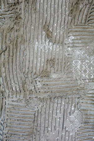 Rusty concrete surface with striped relief. Texture with engraved lines on urban cement wall. Txture of dried embossed cement from fallen off wall tiles Stock fotó