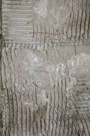 Rusty concrete surface with striped relief. Texture with engraved lines on urban cement wall. Txture of dried embossed cement from fallen off wall tiles