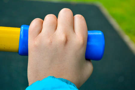 Close up of child hand holding handle of childrens sports equipment on playground. Concept of healthy lifestyle from young age Stockfoto