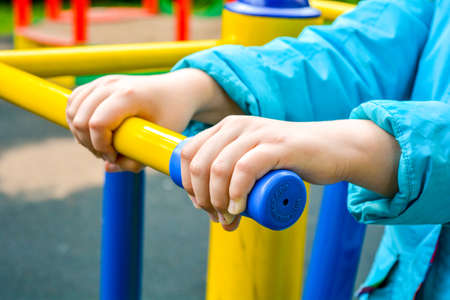 Close up of child hands holding handle of childrens sports equipment on playground. Concept of healthy lifestyle from young age Stockfoto
