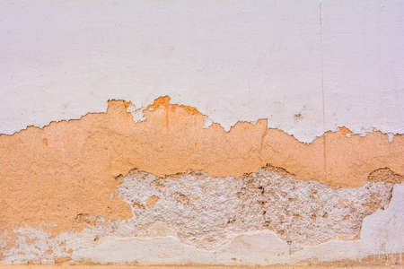 Texture of dirty destroyed concrete wall with exfoliated layer of white and orange paint Banco de Imagens