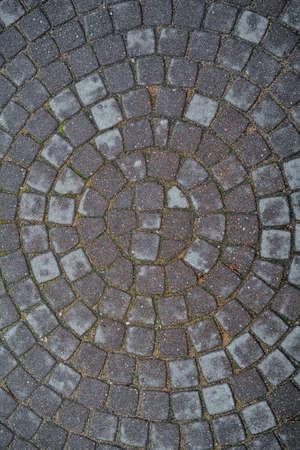Circular texture of square stone floor called Sanpietrini or Sampietrini. Urban cobblestone paving laid out of circles