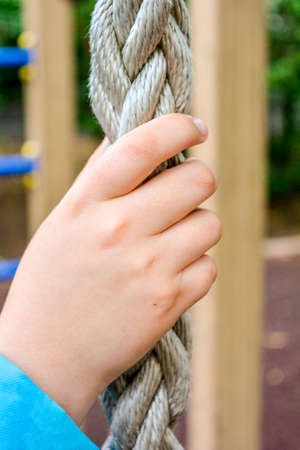 Close up of child hand clings to thick braided rope for climbing of children's sports equipment on children's playground. Concept of healthy lifestyle from young age Stock Photo - 128888512