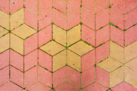 Red and yellow road tiles on city street pavement with growing grass in mortar. Road construction background. Cobblestone pathway paved with yellow and red rhombus bricks. Road cover surface texture Stockfoto