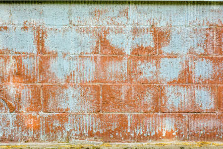 Texture of red corrugated brick wall with white peeling paint. Background image featuring siding brickwork with fluted texture