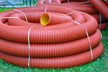 Coils of new red plastic pipe with rain drops on city lawn with green grass. Red plastic tubing for underground cable protection. First floor of skein of red corrugated tube. Plastic pipes background Stock fotó