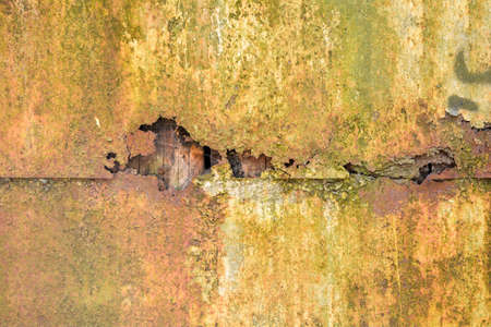 Detail of broken rusty corroded metal wall. Old orange metal texture background