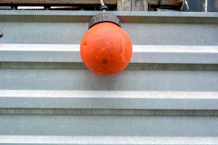 Die kugelförmige Laterne des roten Signals hängt an einem elektrischen Kabel am gestreiften Metallzaun des Stadtgebäudes. Schmutzige rote Gebäudelampe und Metallwand